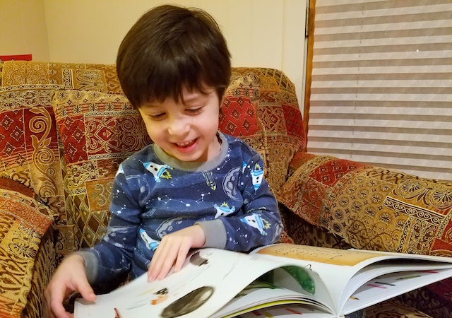 Nico smiles while reading The Day the Crayons Quit