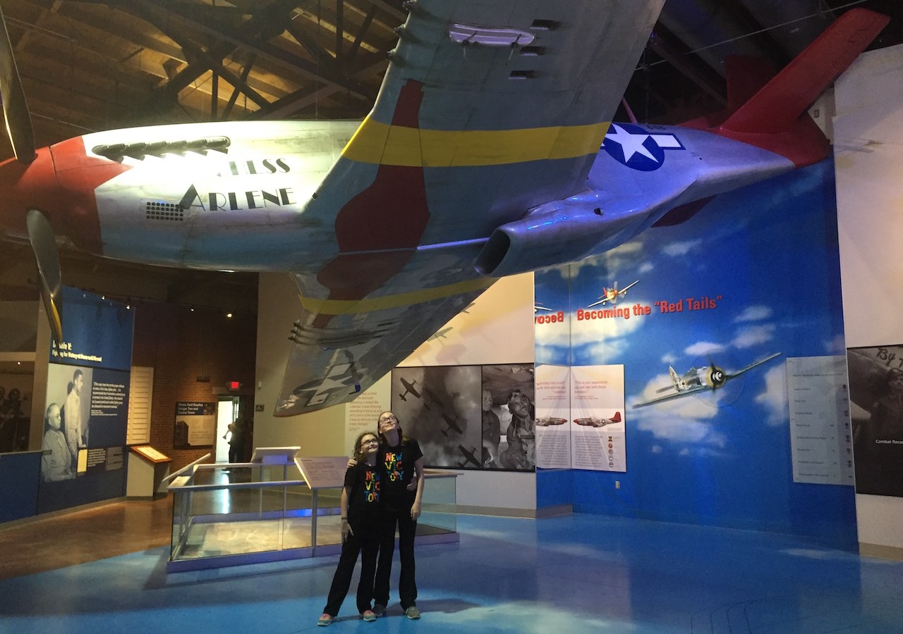 Genevieve and Phoebe stand dwarfed beneath a red-tailed aircraft suspended from the ceiling