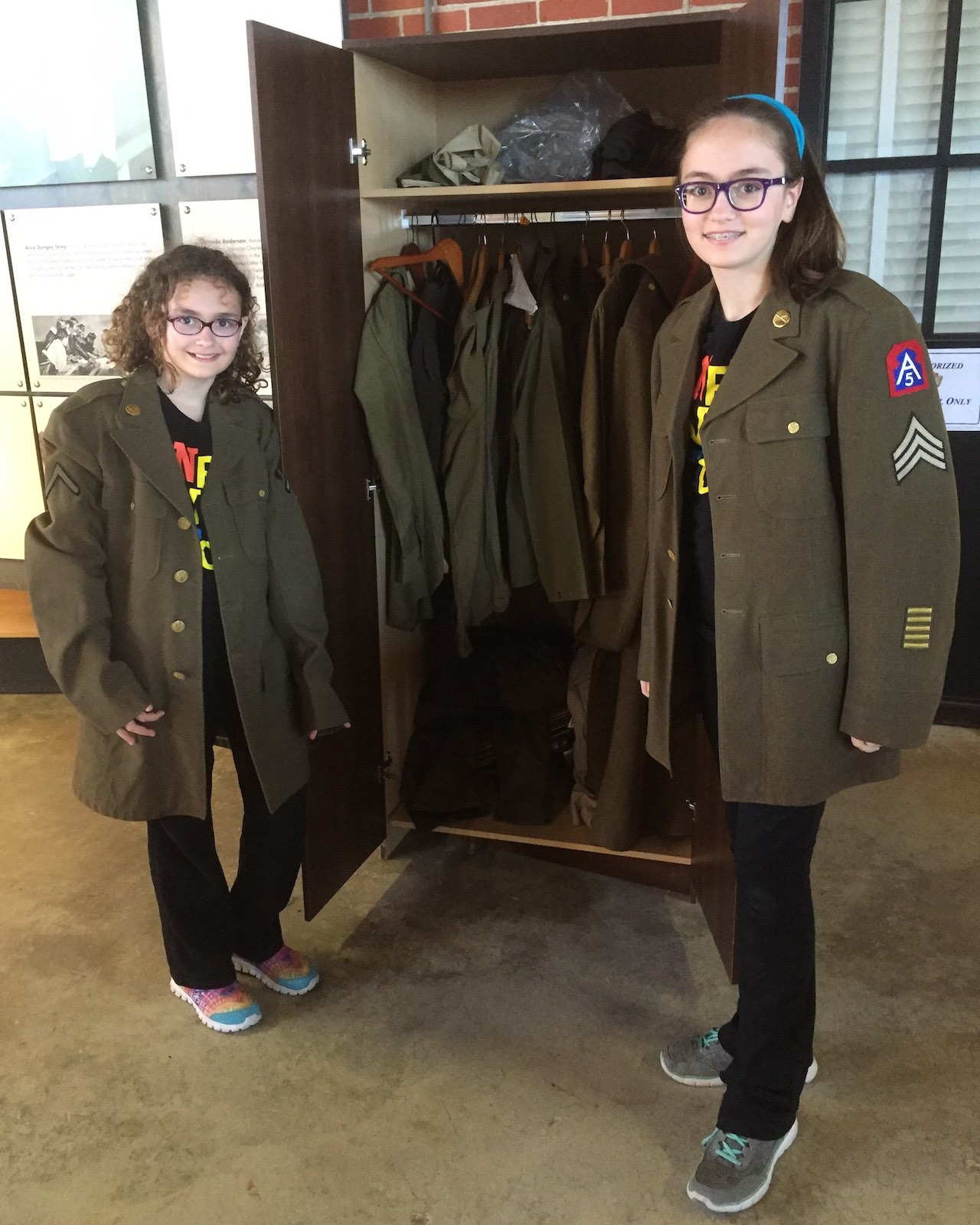Genevieve and Phoebe try on oversized military uniforms