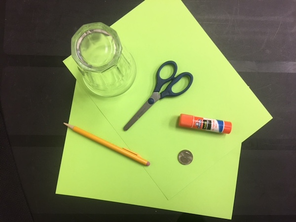 A glass, two sheets of paper, a pencil, a pair of scissors, a glue stick and a coin