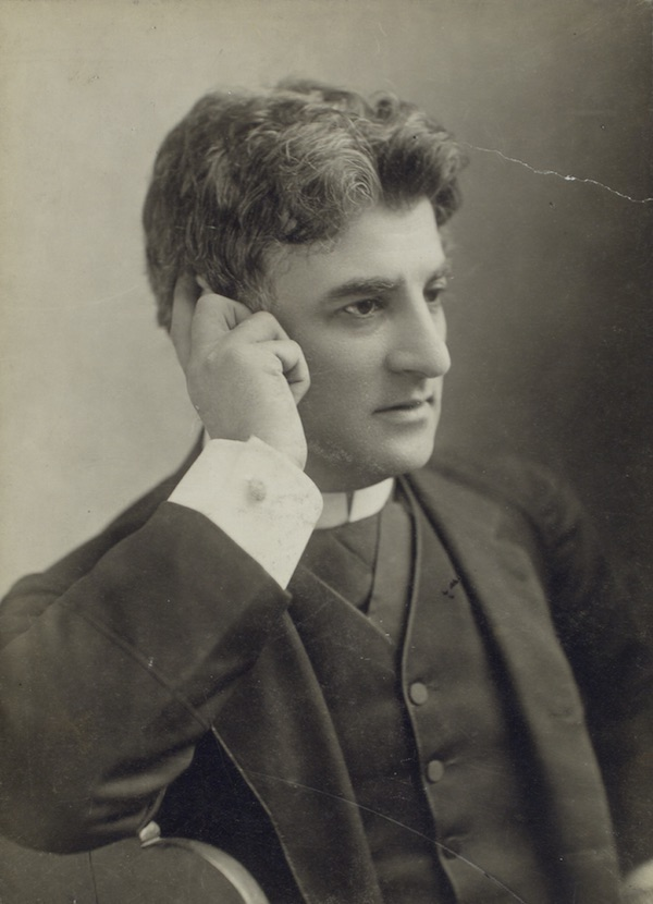 Black and white photo of man in dark suit and priest collar