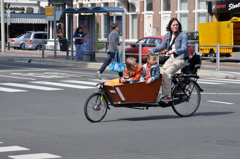 A woman on a bike, pushing two kids in a cart