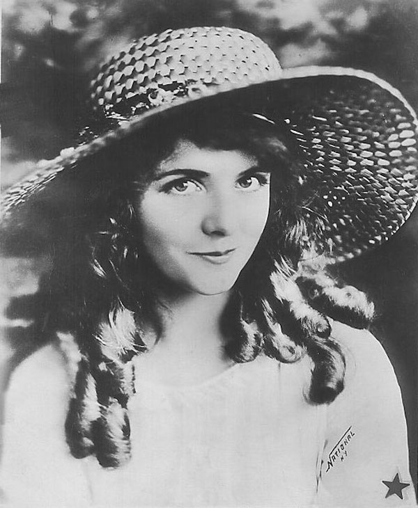 Black and white photo of woman in large straw hat