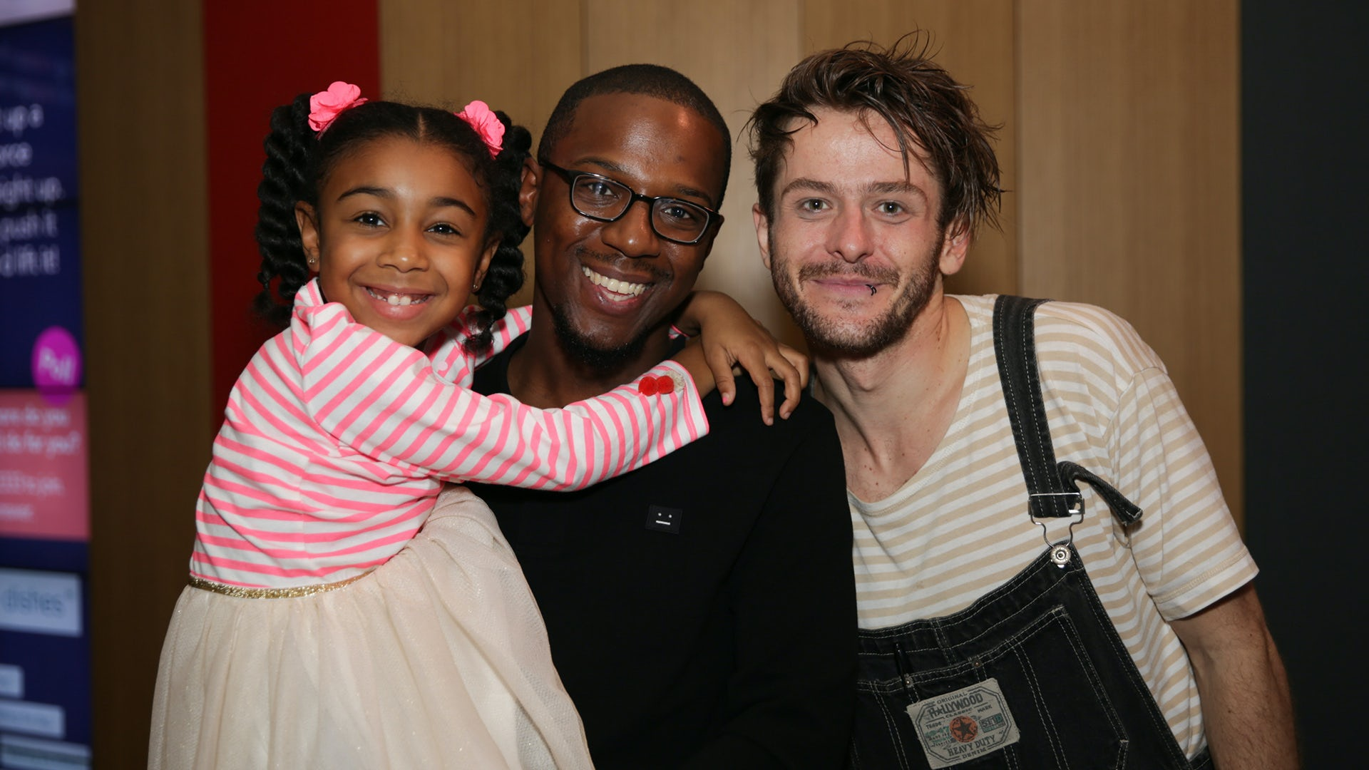 Smiling dad and daughter pose for a post-show photo with a cast member.