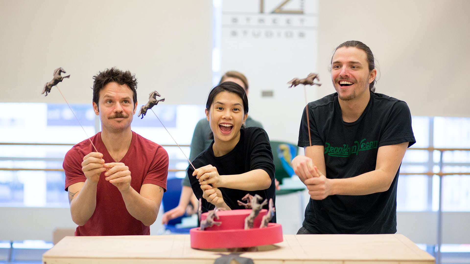 Three actors operate toy horse rod puppets in a scene from the LabWorks project, Horsetale.