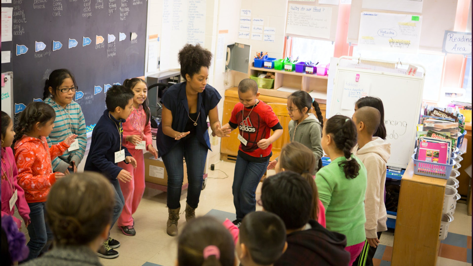 Teacher and students stand in a circle participating in a Classroom Workshop.