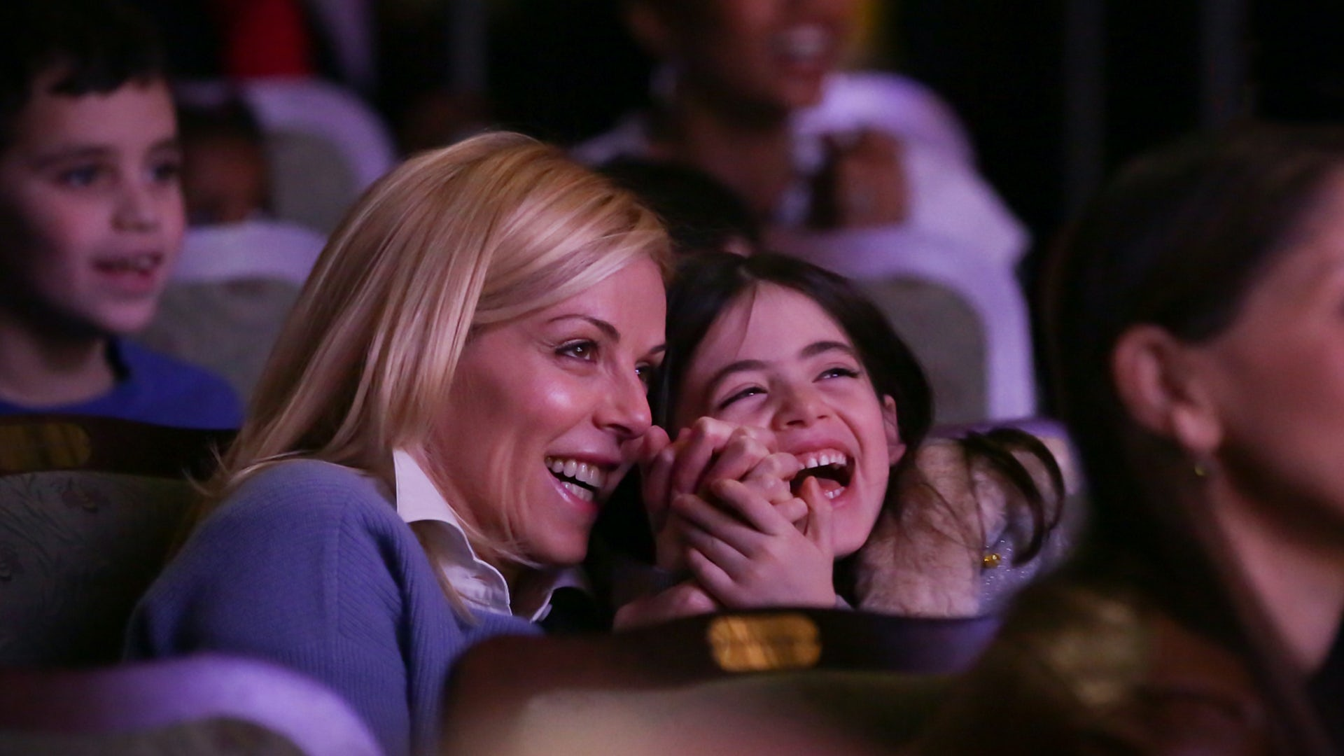 A Mom and daughter react to a performance with smiles and laughter.