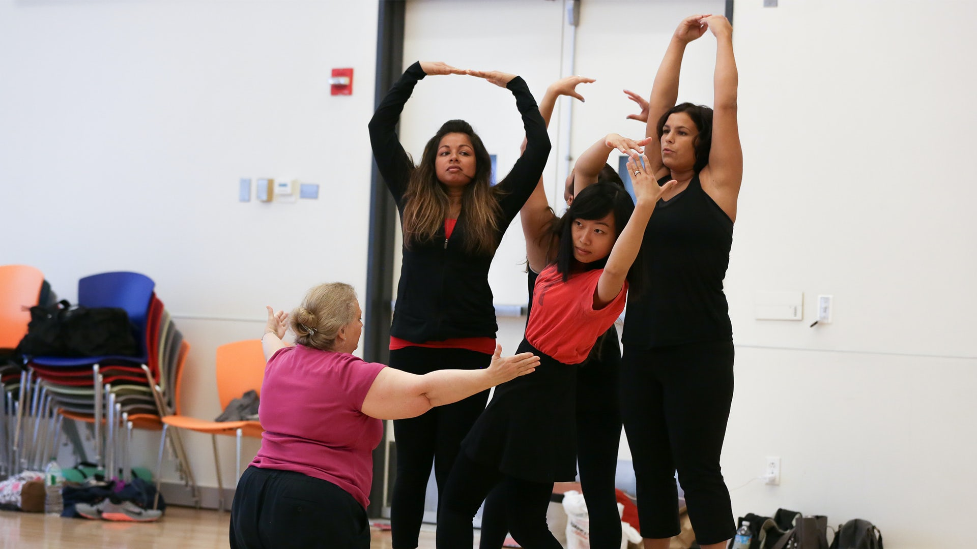 An educator instructs her colleagues to pose during a dance Professional Development workshop.