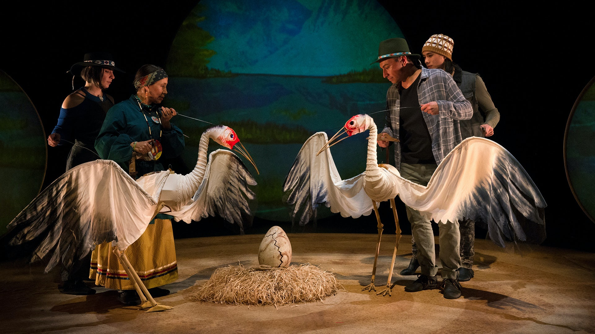 Several cast members operate two large crane puppets in a scene from Ibex Puppetry's Ajijaak on Turtle Island.