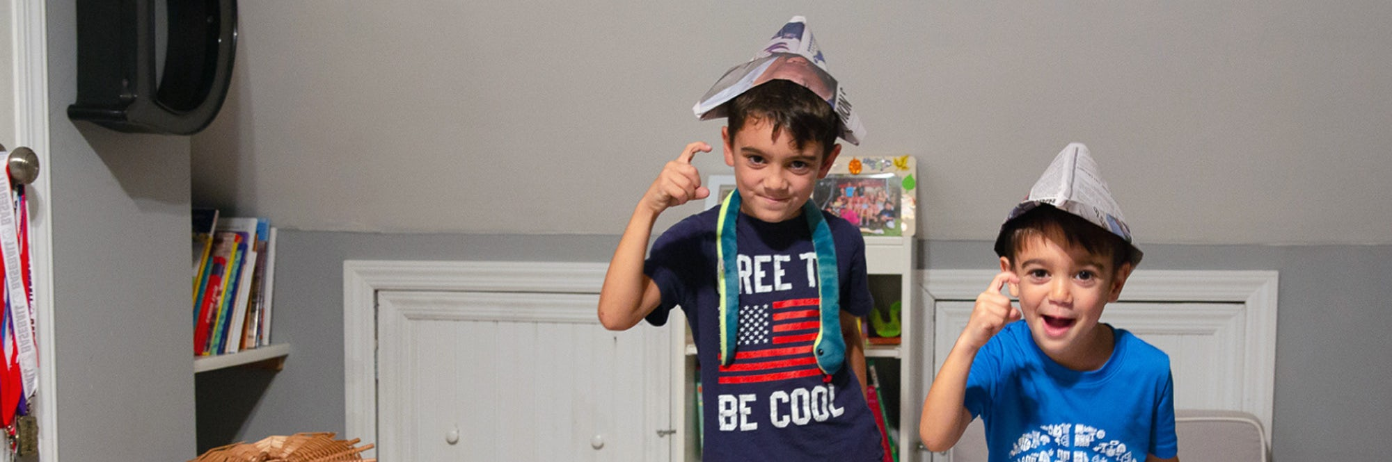 Two young boys wear newspaper hats and act like pirates to complete a mission in The Great New Victory Scavenger Hunt.