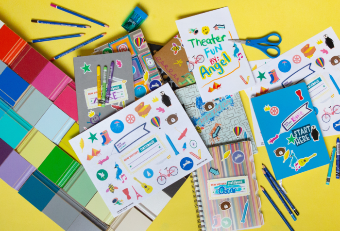 Several colorful New Victory Notebooks decorated with stickers on a yellow background.