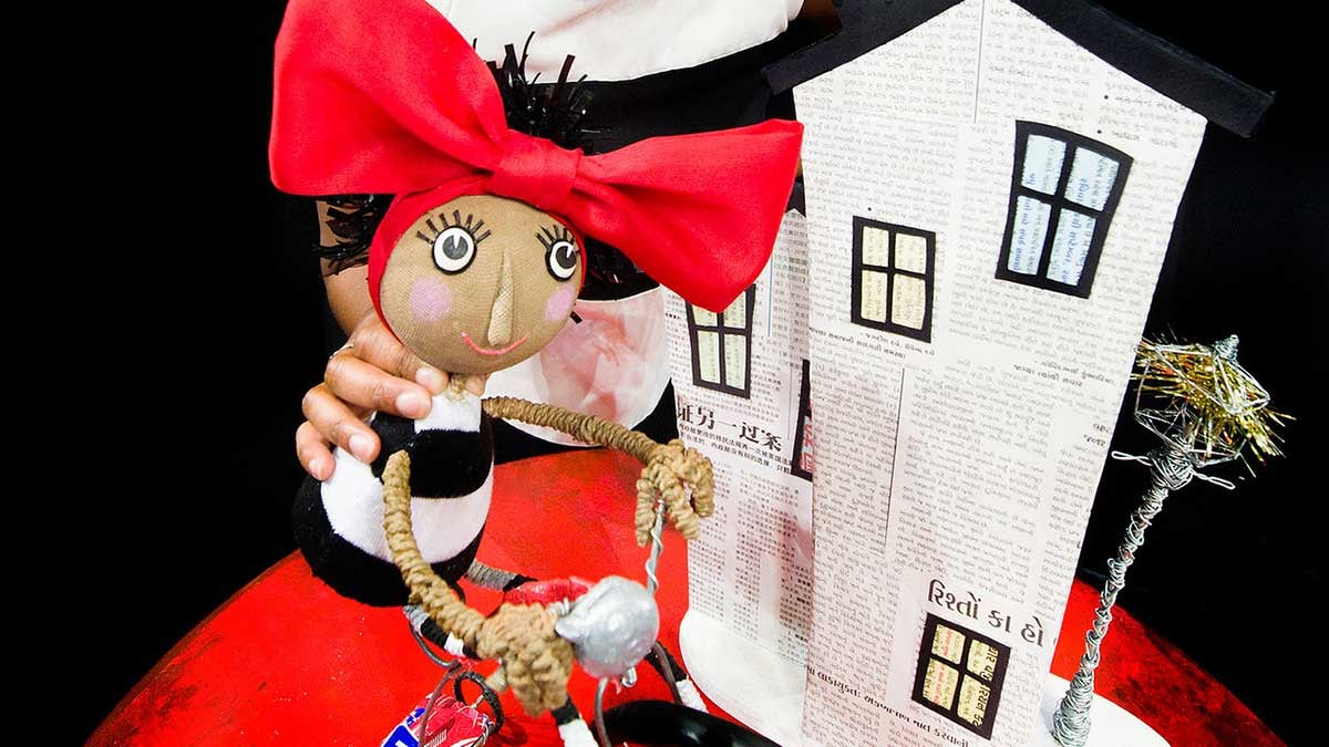 A puppet with a striped dress in front of a newspaper house and wire tree
