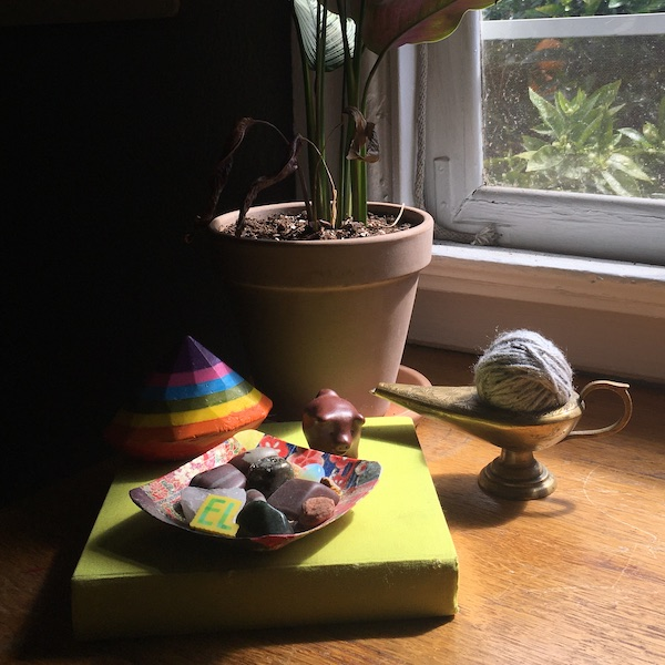 A potted plant, a book, a bowl of stones, a ball of yarn, a brass lamp