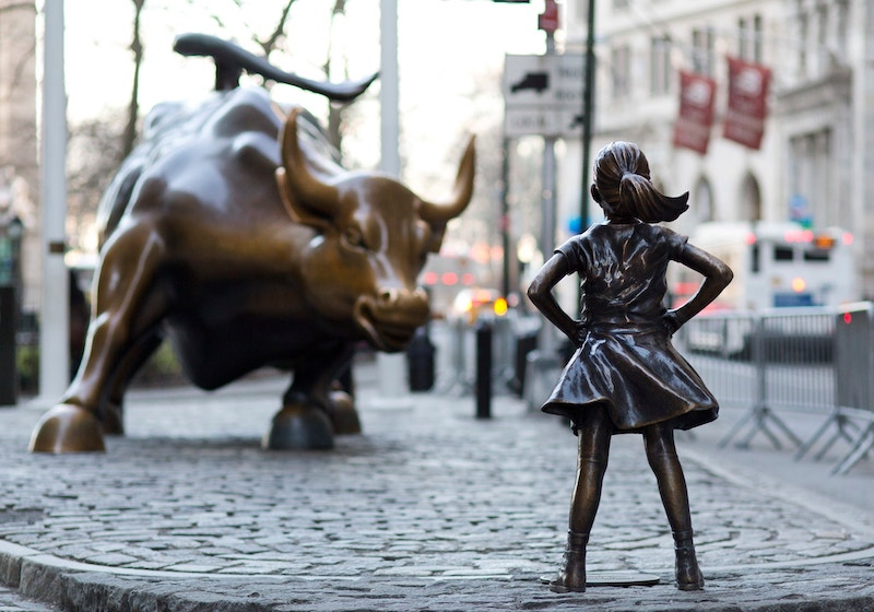A bronze statue of a young girl standing defiantly, facing a charging bull