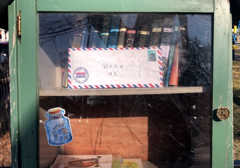 A letter nestled into a free, little library station