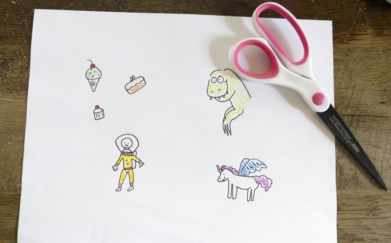 A white sheet of paper with drawings of a flying unicorn, a dinosaur, an astronaut and desserts, with a pair of scissors on top