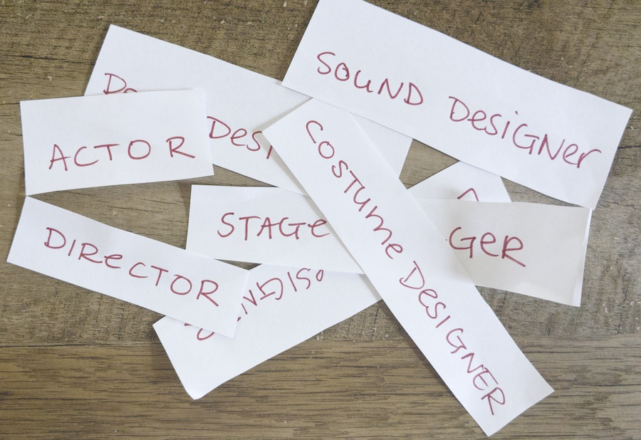 Small pieces of paper with various theater-making roles written on them