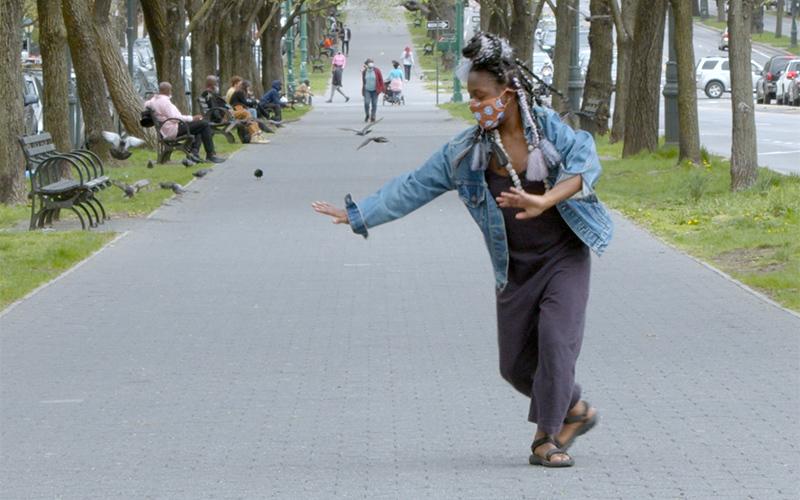 nicHi douglas dances on a pathway in a park.